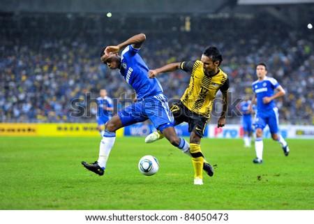 KUALA LUMPUR, JULY 21 : Chelsea's Nathaniel Chalobah and Malaysian Amri Yahyah in action during a preseason match against Malaysia on July 21, 2011 in Kuala Lumpur, Malaysia. Chelsea won 1-0 - stock photo
