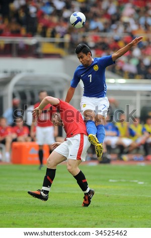 KUALA LUMPUR- JULY 18: Wayne Rooney of Manchester United team and Malaysian, Aidil Zafuan (7) in action during friendly match against Malaysia, July 18, 2009 in Kuala Lumpur. - stock photo