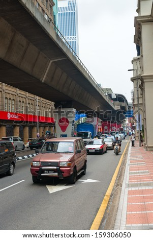KUALA LUMPUR - JUN 15: City street with cars and  monorail way under road on Jun 15, 2013 in Kuala Lumpur, Malaysia. Three separate rail systems with underground, elevated or at-grade lines. - stock photo