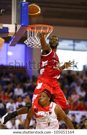 KUALA LUMPUR - JUNE 02: Vincent Crews (Beermen) jumps above Tiras Wade (Dragons) to block his lay up shot in a playoff match in the ASEAN Basketball League on June 02, 2012 in Kuala Lumpur, Malaysia. - stock photo