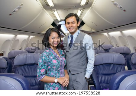KUALA LUMPUR, MALAYSIA - APRIL 23, 2014: Malaysian Airline crew members posing in Boeing 737 aircraft after landing on April 23, 2014. Malaysian Airline System is the flag carrier airline of Malaysia - stock photo