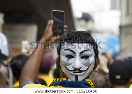 Kuala Lumpur, Malaysia 30 August 2015 : Yellow shirt Supporter of Bersih4 Rally for Free Fair Elections takes selfie with mask. Bersih organized Rallies 29/30 August 2015 in cities around Malaysia