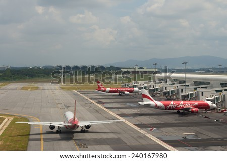 KUALA LUMPUR, MALAYSIA - DECEMBER 10, 2014 : Air Asia Airplanes embarking at KLIA2 airport. AirAsia QZ8501 from Indonesia to Singapore reported lost contact with air traffic control, 28 December 2014. - stock photo