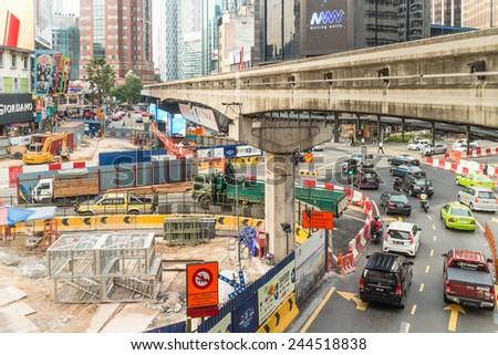 Kuala Lumpur, Malaysia - December 17 2014: cars pass through an intersection in Bukit Bintang in the heart of Kuala Lumpur. The construction site is for the upcoming MRT extension. - stock photo