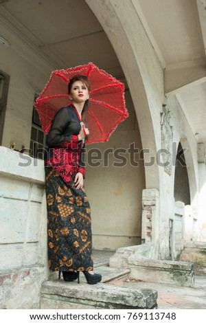 Kuala Lumpur, Malaysia - December 5, 2017: Fashion portraiture of young beautiful malay woman wearing modern kebaya. Image contain certain grain or noise and soft focus - illustrative editorial.