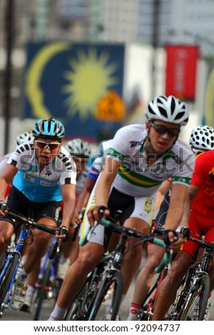 KUALA LUMPUR, MALAYSIA-FEBRUARY 15: Cyclists pedal their way in front of Malaysian flag background during the Le Tour de Langkawi competition in Kuala Lumpur,Malaysia on February 15,2009. - stock photo