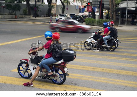 Kuala Lumpur, Malaysia - February 7, 2016. Two motorcycles waiting on red light and one motion blurred car on traffic. - stock photo