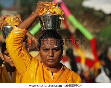 Kuala Lumpur, Malaysia, January 27 2013: A Hindu devotee carries a pot of milk on her head during Thaipusam festival to fulfill their vows and offer thanks to the deities. - stock photo