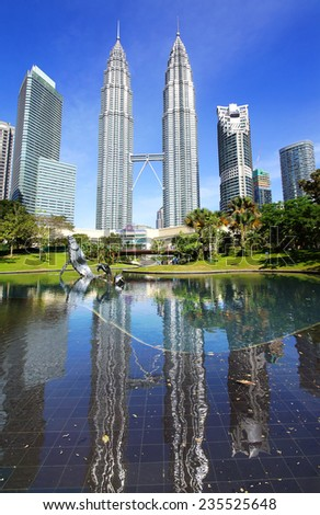 KUALA LUMPUR, MALAYSIA - JANUARY 31, 2014: Park with fountains at Petronas towers. A green and quiet oasis in the city centre. Designed by the brazilian landscape artist, the late Roberto Burle Marx.  - stock photo