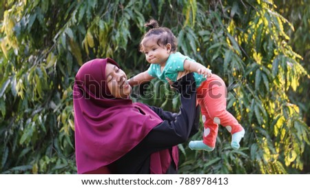 Kuala Lumpur,Malaysia - January 8th,2018 : A young stranger girl wear a wet scarf and carrying a adorable baby girl cheerfully in front of a big green tree.