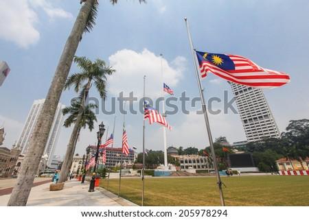 "KUALA LUMPUR, MALAYSIA - JULY 20, 2014: A nation in mourning. The Malaysian ""Jalur Gemilang"" flags flown at half mast at Dataran Merdeka, Kuala Lumpur following the incident of Malaysia Airlines MH17. - stock photo"