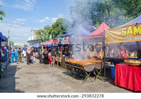 Kuala Lumpur,Malaysia - July 5, 2015: People seen walking and buying foods around the Ramadan Bazaar.It is established for muslim to break fast during the holy month of Ramadan. - stock photo