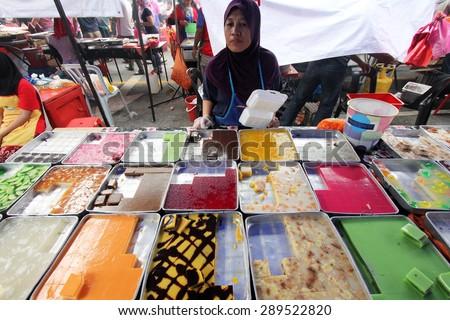 KUALA LUMPUR, MALAYSIA : JUNE 19, 2015 - A street hawker selling a variety of Malaysian kuih pastry at a ramadhan bazaar in Kuala Lumpur, Malaysia. - stock photo