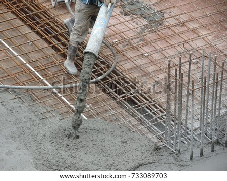 KUALA LUMPUR, MALAYSIA -JUNE 16, 2017: Construction workers pouring wet concrete using concrete spider hose from concrete pumping machine into floor slab form work at the construction site.