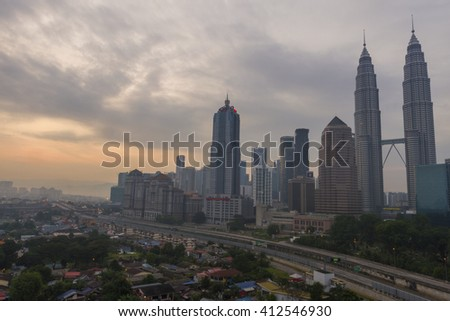 KUALA LUMPUR, MALAYSIA : JUNE 6, 2015 - Kuala Lumpur city skyline during sunrise with lit up buildings. Image contain grain, noise and soft focus due long exposure