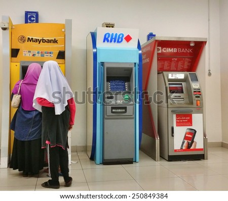 KUALA LUMPUR, MALAYSIA-JUNE 22, 2014: Unidentified people withdraw money from ATM machines in Kuala Lumpur. Maybank, RHB Bank and CIMB Bank are three top banks in Malaysia. - stock photo