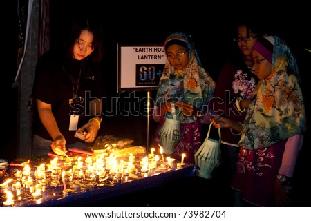 KUALA LUMPUR, MALAYSIA-MAR 26:Participant of Earth Hour Campaign wait to light-up the lantern on Mar 26, 2011 in Kuala Lumpur.More than 4,000 cities in 131 countries celebrate Earth Hour