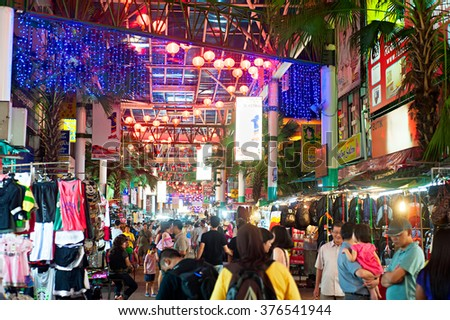 KUALA LUMPUR, MALAYSIA - MARCH 30, 2012: People on Petaling Street  in Kuala Lumpur. The street is a long market which specialises in counterfeit clothes, watches and shoes. Famous tourist attraction - stock photo