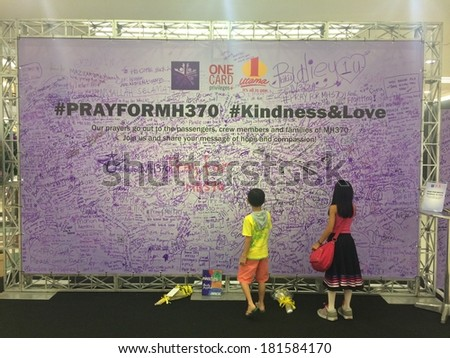 KUALA LUMPUR, MALAYSIA - MARCH 14, 2014: two kids signing a billboard for the safe return of Malaysia Airlines MH370 which went missing on March 8 2014. MH370 remains missing to date  - stock photo