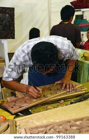 KUALA LUMPUR, MALAYSIA - MARCH 30: Wood carving demonstrations by exhibitors staff during National Craft Day 2012 at the Kuala Lumpur Craft Complex on March 30, 2012 in Kuala Lumpur, Malaysia - stock photo