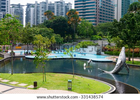 KUALA LUMPUR, MALAYSIA - 02 NOV 2014: KL City park with whale statues and children in the swimming pool, green grass and trees. Modern buildings in the background. - stock photo