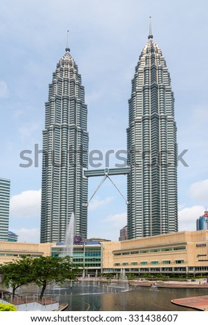 KUALA LUMPUR, MALAYSIA - 02 NOV 2014: Petronas Twin Towers, Symfoni Lake and Suria KLCC shopping mall. A famous building,beautiful architecture with a walkway between the two towers.