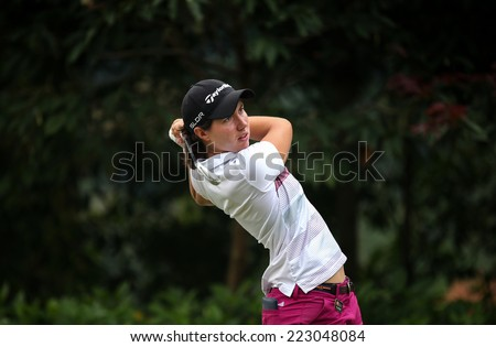 KUALA LUMPUR, MALAYSIA - OCTOBER 11, 2014: Carlota Ciganda of Spain tees off at the fourth hole of the KL Golf & Country Club during the 2014 Sime Darby LPGA Malaysia golf tournament. - stock photo