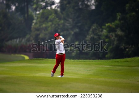 KUALA LUMPUR, MALAYSIA - OCTOBER 10, 2014: Eun-Hee Ji of South Korea plays on the fairway of the ninth hole of the KL Golf & Country Club at the 2014 Sime Darby LPGA Malaysia golf tournament. - stock photo