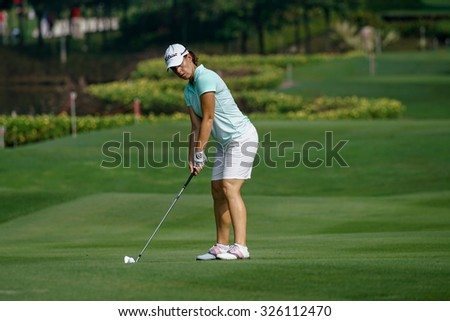 KUALA LUMPUR, MALAYSIA - OCTOBER 09, 2015: France's Karine Ischer prepares to hit from the 6th hole fairway at the KL Golf & Country Club at the 2015 Sime Darby LPGA Malaysia golf tournament. - stock photo