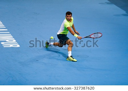 KUALA LUMPUR, MALAYSIA - OCTOBER 02, 2015: Grigor Dimitrov of Bulgaria hits a backhand return in his match at the Malaysian Open 2015 tennis tournament held at the Putra Stadium, Malaysia. - stock photo