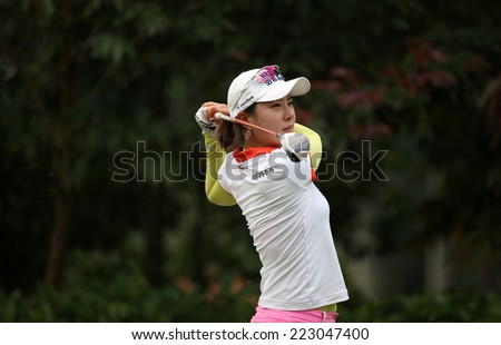 KUALA LUMPUR, MALAYSIA - OCTOBER 11, 2014: Hee Young Park of South Korea tees off at the fourth hole of the KL Golf & Country Club during the 2014 Sime Darby LPGA Malaysia golf tournament. - stock photo