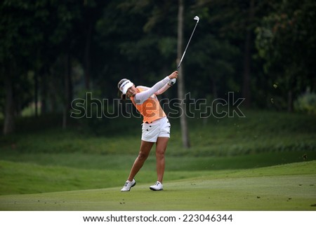 KUALA LUMPUR, MALAYSIA - OCTOBER 11, 2014: Jenny Shin of the USA makes a shot from the fairway of the ninth hole of the KL Golf & Country Club during the 2014 Sime Darby LPGA Malaysia golf tournament. - stock photo