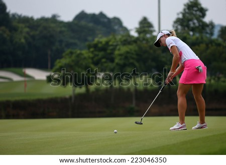 KUALA LUMPUR, MALAYSIA - OCTOBER 11, 2014: Jodie Ewart Shadoff of England putts on the green of the ninth hole of the KLGC Club during the 2014 Sime Darby LPGA Malaysia golf tournament. - stock photo