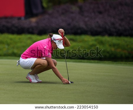KUALA LUMPUR, MALAYSIA - OCTOBER 10, 2014: Lee-Anne Pace of South Africa places the ball for a putt at the 18th hole of the KL Golf & Country Club at the 2014 Sime Darby LPGA Malaysia golf tournament. - stock photo