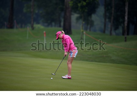 KUALA LUMPUR, MALAYSIA - OCTOBER 11, 2014: Morgan Pressel of the USA putts on the green of the third hole of the KL Golf & Country Club during the 2014 Sime Darby LPGA Malaysia got tournament. - stock photo