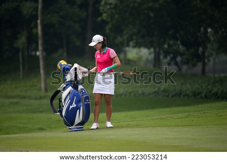 KUALA LUMPUR, MALAYSIA - OCTOBER 10, 2014: Park Hee Young of South Korea select her club to play at the ninth hole of the KL Golf & Country Club at the 2014 Sime Darby LPGA Malaysia golf tournament. - stock photo
