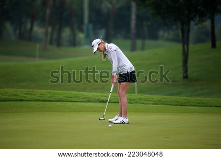 KUALA LUMPUR, MALAYSIA - OCTOBER 11, 2014: Paula Creamer of the USA putts on the green of the third hole of the KL Golf & Country Club during the 2014 Sime Darby LPGA Malaysia got tournament. - stock photo