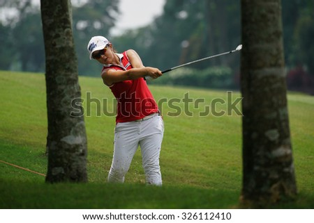 KUALA LUMPUR, MALAYSIA - OCTOBER 09, 2015: South Korea's Sei Young Kim hits from the rough of the 6th hole fairway at the KL Golf & Country Club at the 2015 Sime Darby LPGA Malaysia golf tournament. - stock photo