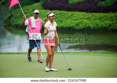 KUALA LUMPUR, MALAYSIA - OCTOBER 10, 2015: USA's Alison Lee reacts after her putt at the 18th hole of the Kuala Lumpur Golf & Country Club during the 2015 Sime Darby LPGA Malaysia golf tournament. - stock photo