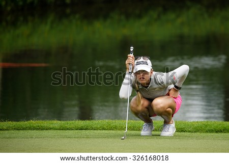 KUALA LUMPUR, MALAYSIA - OCTOBER 10, 2015: USA's Jessica Korda lines her putt at the green of the 18th hole of the KL Golf & Country Club during the 2015 Sime Darby LPGA Malaysia golf tournament. - stock photo