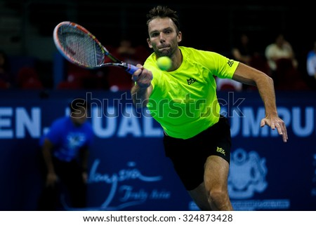KUALA LUMPUR, MALAYSIA - SEPTEMBER 30, 2015: Ivo Karlovic of Croatia hits a forehand return in his match at the Malaysian Open 2015 Tennis tournament held at the Putra Stadium, Malaysia. - stock photo