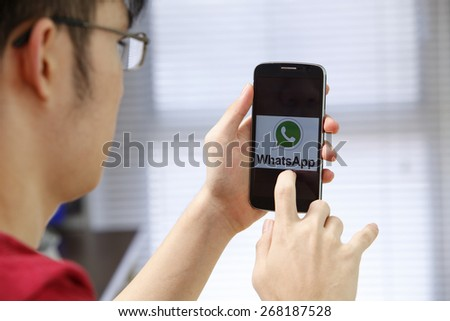 Kuala Lumpur,Malaysia 9th April 2015,Man holding a smartphone  with social Internet service WhatsApp on the screen.  - stock photo