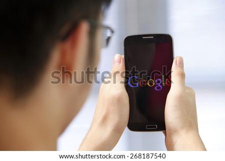 Kuala Lumpur,Malaysia 9th April 2015, Young man Using Google Web Search on her Smart Phone. - stock photo