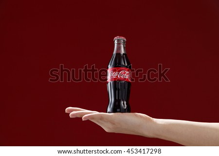 Kuala Lumpur,Malaysia 11th July 2016, Hand hold a bottle Coca-Cola on red background. Coca Cola drinks are produced and manufactured by The Coca-Cola Company. - stock photo