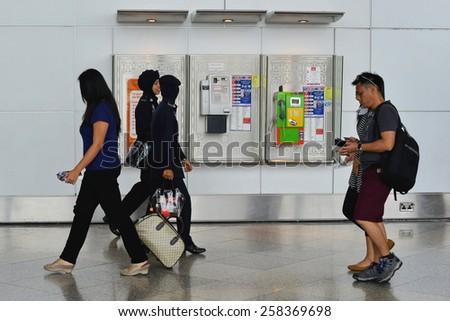 KUALA LUMPUR - MAR 2: Travellers pass through Kuala Lumpur International Airport (KLIA) on Mar 2, 2014 in Kuala Lumpur, Malaysia. KLIA has the capacity to carry 70 million passengers per year. - stock photo
