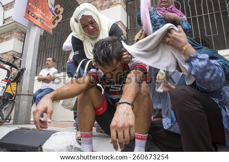 KUALA LUMPUR - MARCH 15 : Harrif Saleh(MAS) being treated by his family after vomiting as completed stage 8 Le Tour de Langkawi 2015 from Kuala Kubu baru to Kuala Lumpur, Malaysia on March 15, 2015. - stock photo