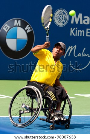KUALA LUMPUR-MARCH 4: Malaysia Olympic Wheelchair players Che Abu Bakar Mat serves during a skilled performance show serves at the BMW Malaysian Open on March 4, 2012 in Kuala Lumpur, Malaysia. - stock photo
