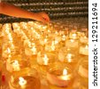 KUALA LUMPUR - MAY 18: A hand lights up candles during the celebration of Wesak day on May 18, 2008 in Kuala Lumpur, Malaysia. Wesak is informally called as Buddha's Birthday. - stock photo