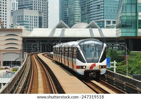 KUALA LUMPUR - MAY 14: A RapidKL LRT train runs on tracks through the city centre on May 14, 2013 in Kuala Lumpur, Malaysia. RapidKL's transport network serves approximately 690,000 passengers daily. - stock photo