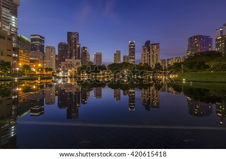 KUALA LUMPUR - MAY 15, 2016: Part of Kuala Lumpur skyline with line of corporate building with reflection from Symphony Lake KLCC